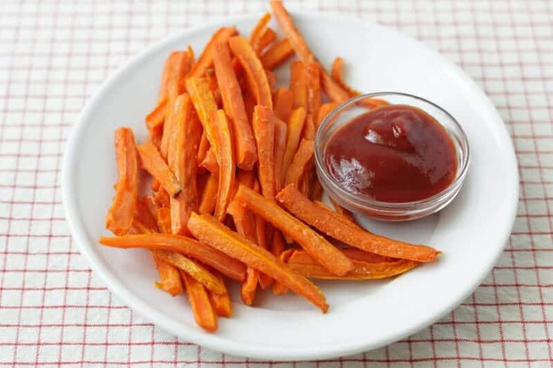 roasted carrot fries on white plate with ketchup