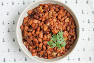 instant pot pinto beans in white bowl with cilantro