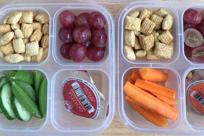 two snack boxes with cereal, grapes, and cheese